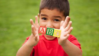 Boy holding A, B, and C wooden blocks