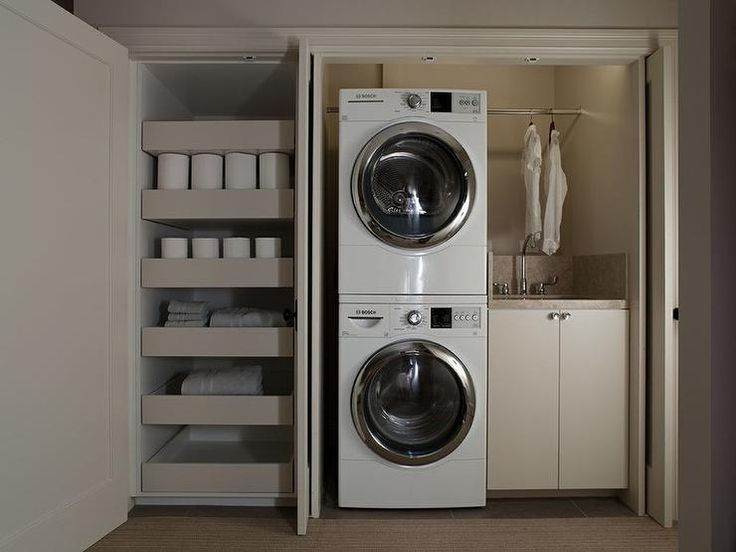 Modern closet is filled with a stacked washer and dryer next to cream cabinets topped with taupe countertop fitted with a stainless steel sink and gooseneck faucet and backsplash under a tension rod situated next to another closet filled with stacked pull-out shelves.