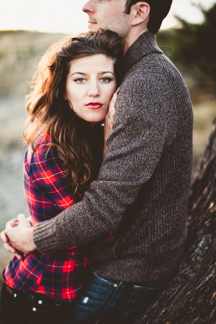 pose - guy stands tall and strong looking out profile. hugs girl.  girl comes in close looks at camera resting head on chest