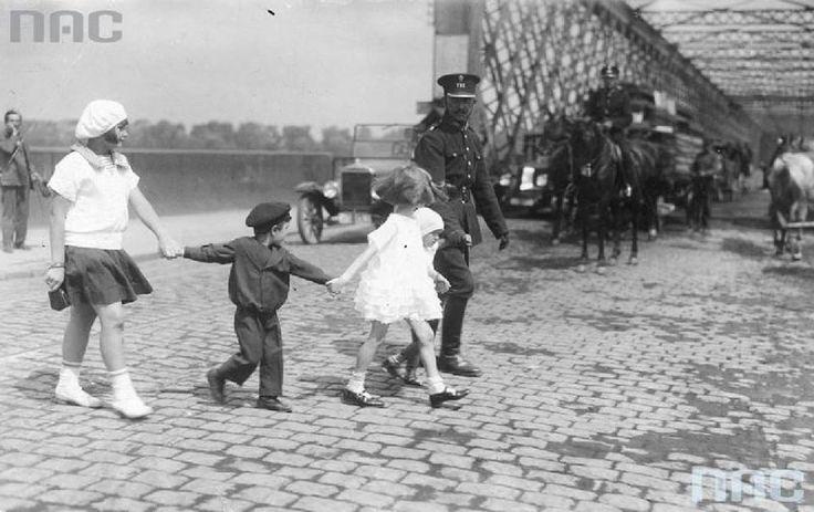 Funkcjonariusze Policji Państwowej podczas pełnienia służby, Policjant przeprowadzający dzieci przez ulicę w pobliżu Mostu Kierbedzia. fot. 1925r., źr. Narodowe Archiwum Cyfrowe.
