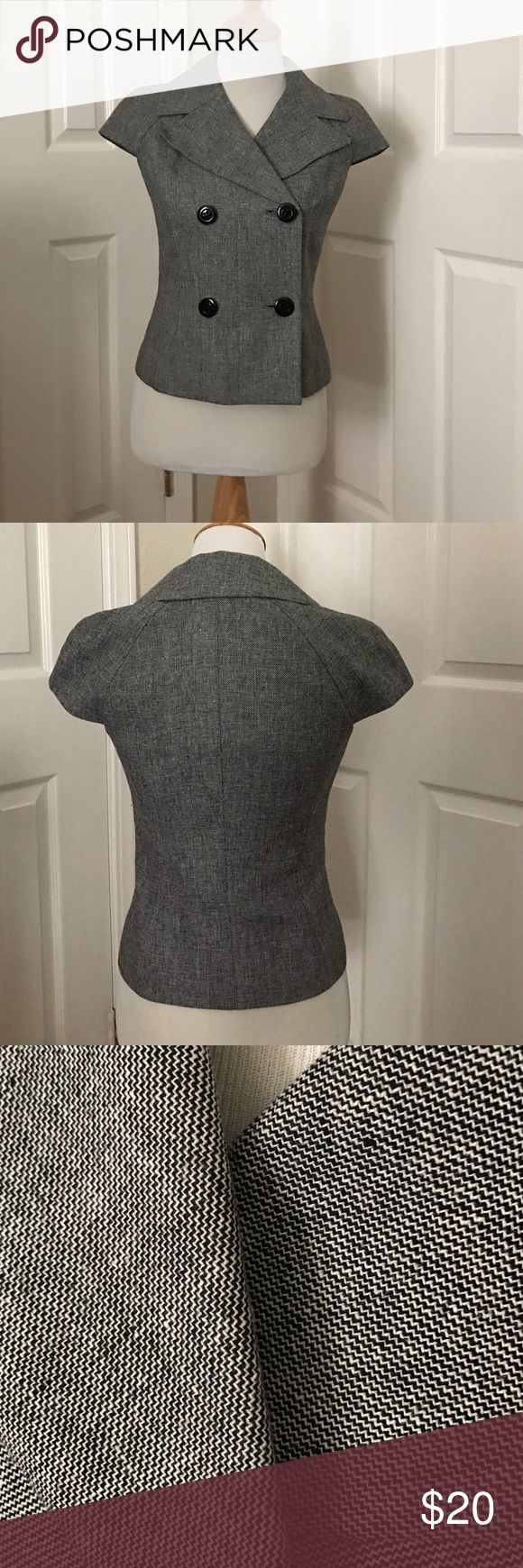 Grey short-sleeved Calvin Klein buttoned top Professional, tailored-looking, sleek, and sharp Calvin Klein top in Gray. 4 black buttons on the front which can be work buttoned or opened for layering a tank/blouse inside. Size 2, true to size. Perfect for work or event, easily dressed up when matched with a pencil skirt or black slacks. Exterior is made up of Linen and Rylan and the interior lining is polyester. Super cute is prestige condition, has only been worn 2-3 times and has only ever…