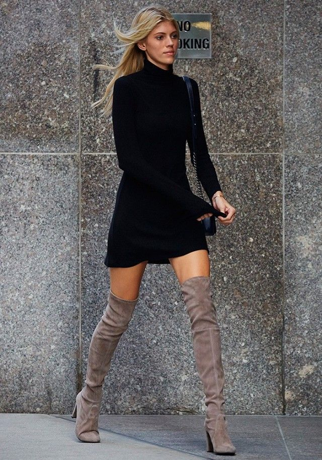 Devon Windsor wears a black minidress with a shoulder bag and neutral suede thigh-high