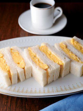 """関西では、溶いて火を通した玉子をフィリングとして用いるのがポピュラーです。このサンドイッチは、ふわとろ感が最高。ポイントは、""""空気を含ませるように卵をしっかり混ぜる""""こと。  【材料】 2人分 角食パン(1.4cm厚さに切る)4枚 卵 2個 マヨネーズ 大さじ1/2杯 マーガリン 適量"""
