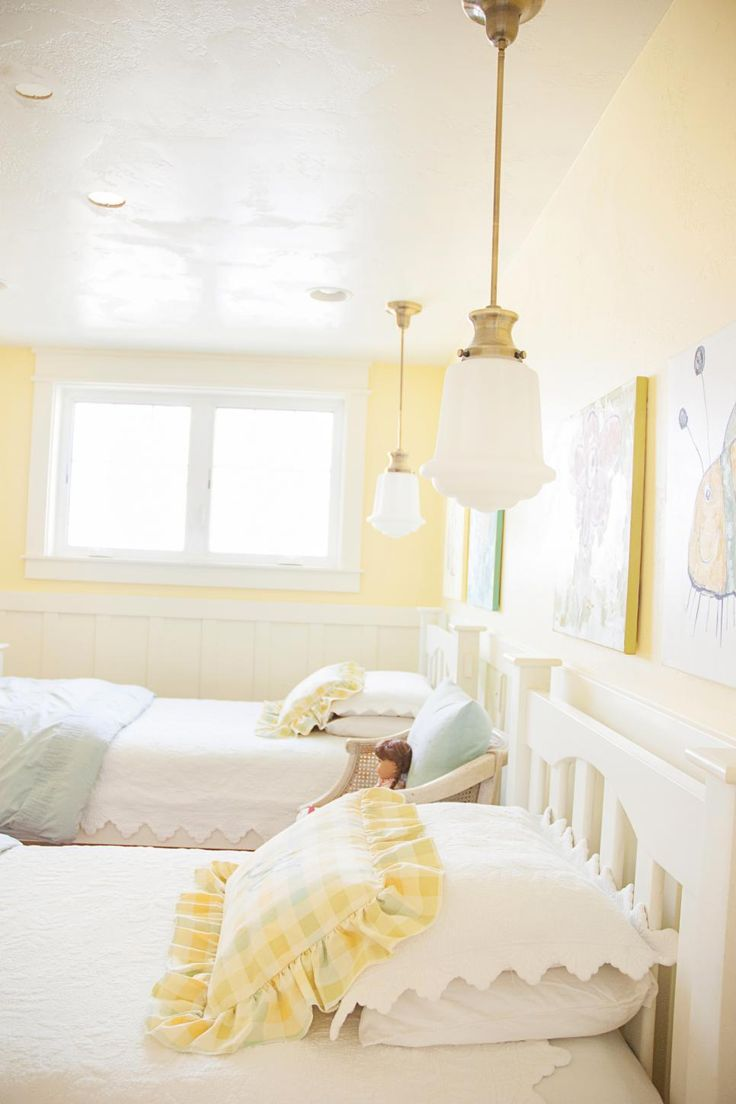 The beautiful color of yellow on the walls in this country-style bedroom is cheery enough for two young girls yet soft enough to grow with them. Pendant lights with individual switches hang above each bed, so the girls can choose to read at night.