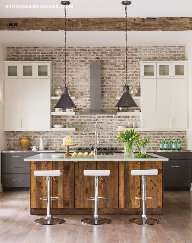 The kitchen's ceiling beams were salvaged from a barn in Pennsylvania, while the new brick on the backsplash was sacked with mortar for a whitewashed look. Chris wrapped the island with reclaimed wood and topped it with a slab of Carrara marble. | Sense of Place | At Home in Arkansas | June 2016