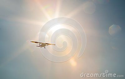 Cessna plane in flight over clear sky with big sun in background.
