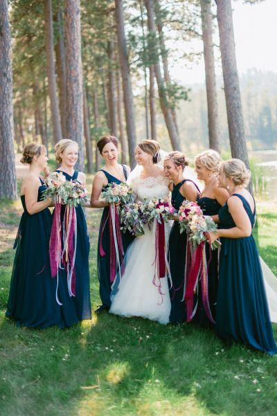 Navy blue, chiffon bridesmaid dresses are perfect for every season. How stunning do they look with these purple ribbon bouquets? Photo: Jeff Sampson Photography