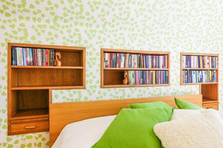 Det stora sovrummets inbyggda bokhylla ramar in den tänkta dubbelsängen och är i ekfanér. Väldigt mycket charm och mycket passande till den underbara tapeten i grönskande blad.