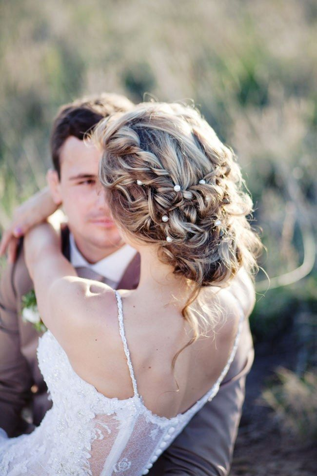 Caroline's sultry wedding upstyle is adorned with sparkly pins holding messy curls into place, featuring a few loose strands at the back for added romance.