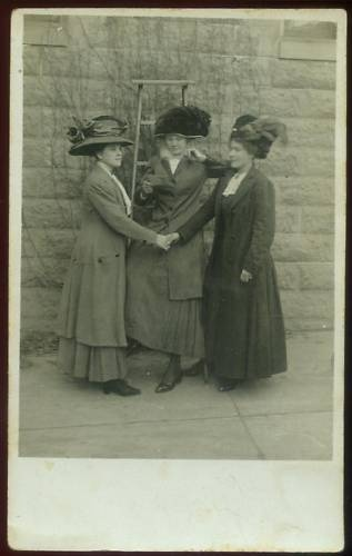 Looks like these fancily dressed women are shaking on a deal or promise. I wonder how much those hats weighed!