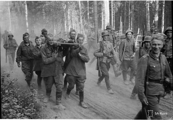 Finnish troops march as Soviet prisoners carry wounded. 2 July 1941.
