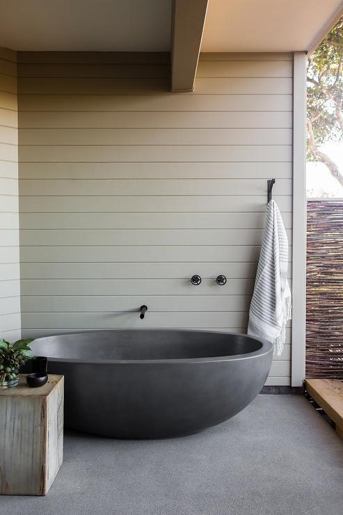 Zen outdoor bathroom features a black freestanding tub under a wall mount tub filler alongside an iron towel hook.
