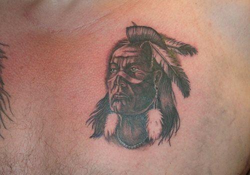 C'est la tête d'un Indien tatouée sur la poitrine. Un petit tatouage de la tête d'un Indien très sérieux. Un dessin très sensuel d'une Indienne.   Cette image est un peu floue.