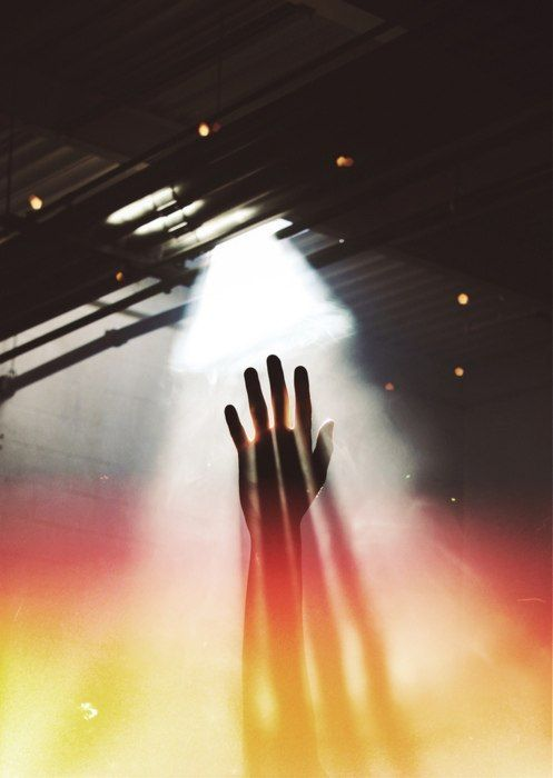 #Hand reaching up through dust motes to escape imprisonment