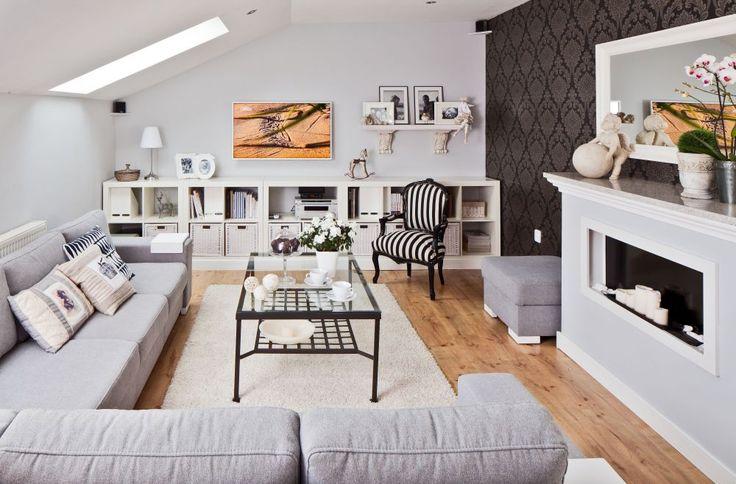 Aranżacja salonu w odcieniach szarości i bieli została przełamana wyrazistą ciemną tapetą na jednej ze ścian.