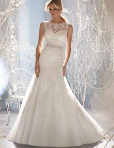It's your day and no one will forget that when you walk down the aisle with a gorgeous gown adorned with crystals. - O Line neck with sheer top adorned with crystals and lace - Waist is accented with