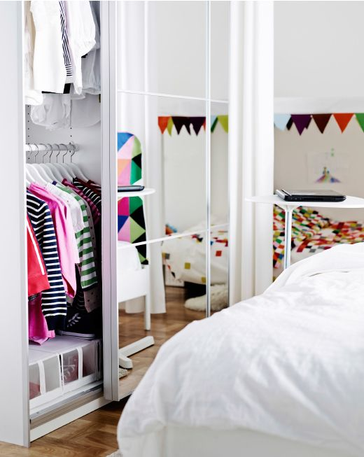 IKEA wardrobes with mirrored sliding doors, partly open to show kids and adult clothes inside.