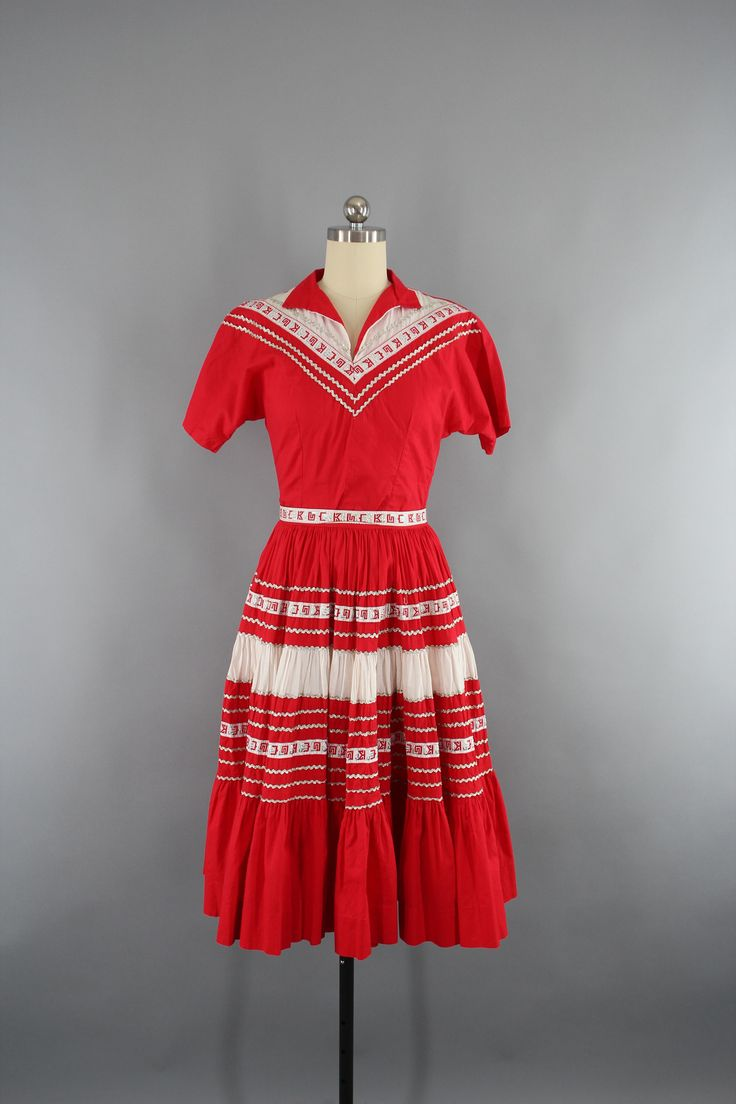Adorable vintage late 1940s to early 1950s square dance dress. Bright red cotton with white and silver trim. Blouse has turned collar and side metal zipper. Skirt has a replaced nylon zipper and butto