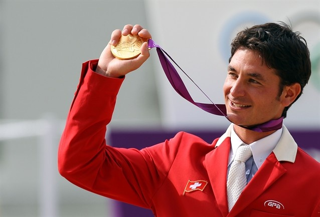Steve Guerdat of Switzerland stands on the podium after winning the Gold medal in the Individual Jumping Equestrian.
