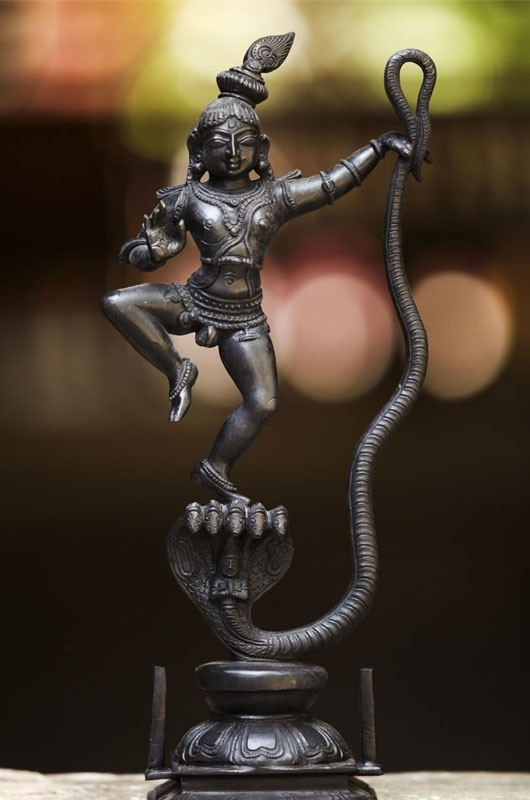 Exceptionally sculptured Kalinga Krishna idol is an art in bronze. According to legends Kalinga, the poisonous snake had occupied and poisoned the river Yamuna causing grave distress to the cowherds and the flora and fauna of Vrindavan. On hearing their plight, young Krishna jumped into the river and overpowered the vile serpent.    If you are a lover of antiques, this finely crafted bronze idol will be value addition to your collection.