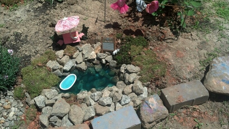 Fairy garden pond made from ol roy dog food bag and rock with a touch of blue food coloring!!!! Fairy bathtub to the side!!!!