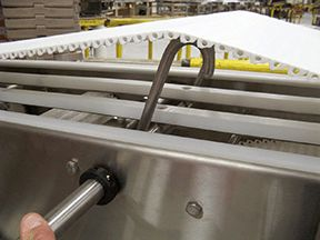 Washdown Conveyor | Sanitary Solutions:  have a variety of features such as clean out ports, spray nozzles, lift up belt, lift out carry way and return way. Standard sanitary features include spaced off frame components, sanitary supports and washdown resistant power transmission components.