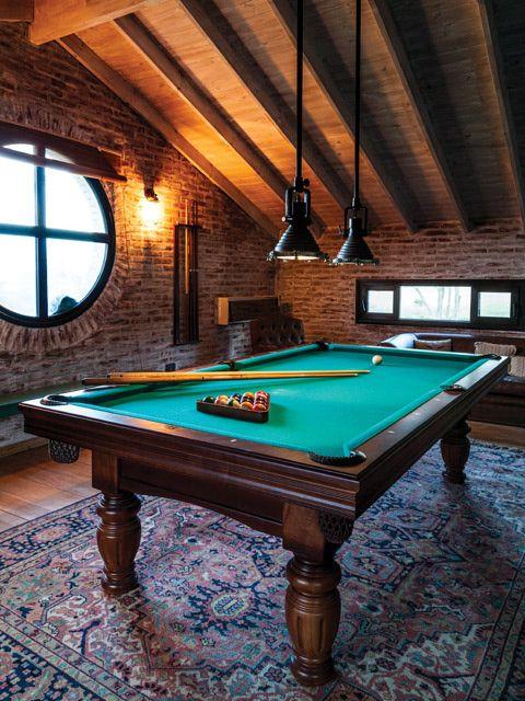 Entrepiso del living de una casa de campo con mesa de pool, paredes de ladrillo, pisos y techo de madera, y ventana ojo de buey.