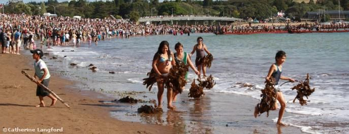 Waitangi Day: Local children make seaweed costumes while crowds gather to watch the wakas gather off Te Beach  © Catherine Langford
