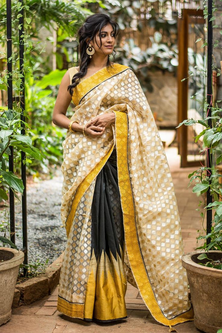 There is something about wearing a half-and-half saree. It is almost like one could not decide on two beautiful drapes and decided to take the world with both! An example for such conquest is this gorgeous chanderi and organza half-and-half saree. The black with yellow spikes gives enough edge while the soft squares take care of the elegance one needs. #black #yellow #chanderi #organza #halfandhalf #saree #India #blouse #houseofblouse