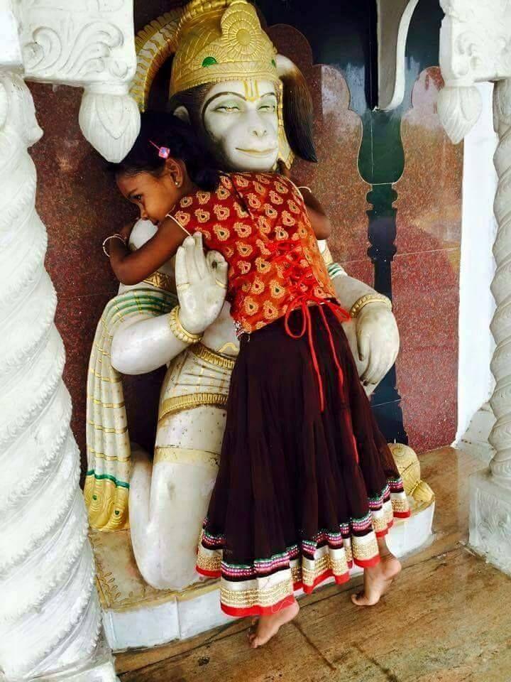 A young devotee hugs statue of Hanuman.