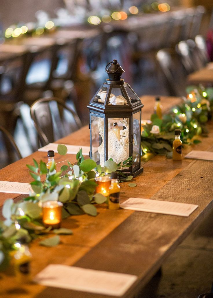 Vintage Lanterns And Green Eucalyptus Garland On Wooden Tables For Wedding Fun Lantern Centerpiece Wedding Wedding Table Garland Wooden Lanterns Centerpieces