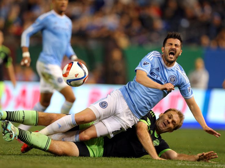New York City FC forward David Villa, top, is tackled by Seattle Sounders FC defender Chad Marshall during the second half of a soccer game in New York. The Sounders won 3-1.  Adam Hunger, USA TODAY Sports