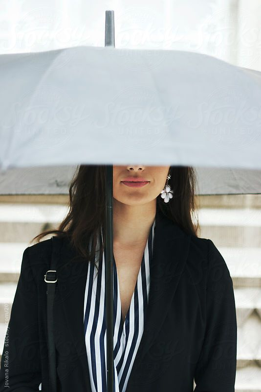 Woman is hiding her face under a big umbrella by Jovana Rikalo for Stocksy United
