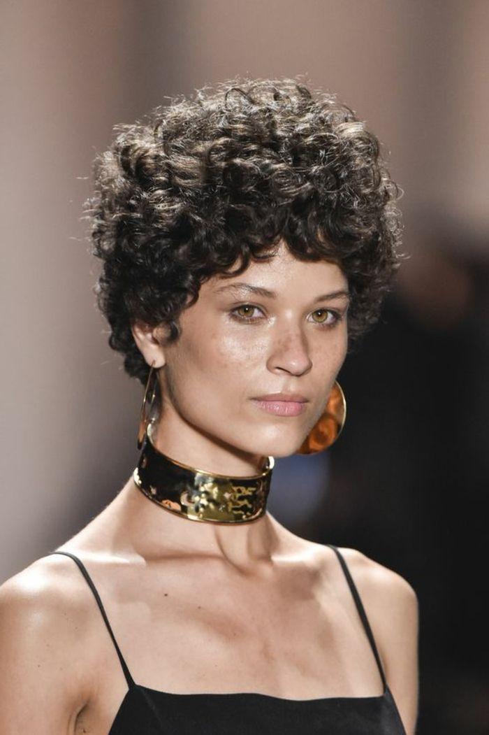 pelo rizado corto, mujer con collar y pendientes, corte pixie voluminoso rizado