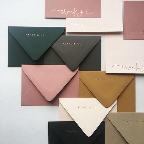 Envelopes in spruce green, olive green, pink, ochre, cream, and black.
