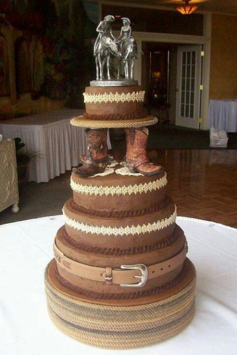 Country wedding cake with cowboy boots and the bride and groom riding horses as the cake topper.