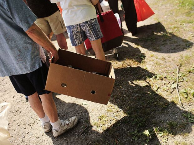 People wait in line with boxes to carry food during a food distribution by the Food Bank of the Southern Tier Mobile Food Pantry on June 20, 2012 in Oswego, New York. (Photo by Spencer Platt/Getty Images)