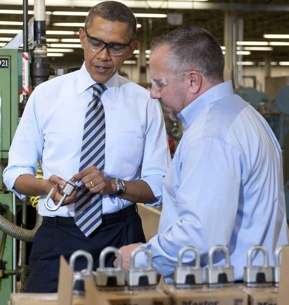 US President Barack Obama (L) examines a lock as he tours the manufacturing facility at Master Lock, maker of security locks, alongside Bob Rice ®, Master Lock Senior Vice President, prior to speaking on the economy in Milwaukee, Wisconsin, February...