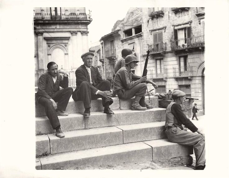 1943- Two American soldiers and three Sicilians sit on the steps of a church in the captured town of Nicosia.