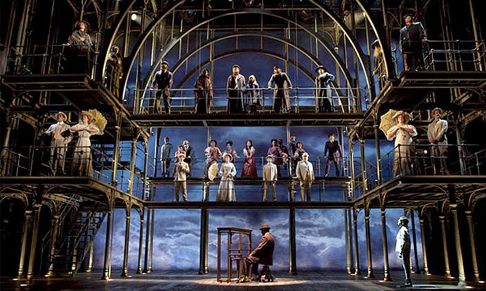 """Ragtime"" Set design by Derek McLane. Straight lines with a curved line on top is contrasting. Different levels, offset from each other. Emphasis on guy at piano center stage. Background contrasts with everything. Near symmetry - the staircase throws it off a bit. Impressionism."