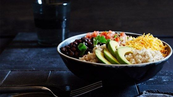 Organic brown rice is topped with black beans, salsa, shredded cheese, and avocado slices for a quick and hearty lunch.