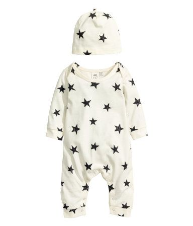 Natural white/stars. CONSCIOUS. Jumpsuit and matching hat in soft, organic cotton jersey. Jumpsuit with overlapping shoulder sections, snap fasteners at