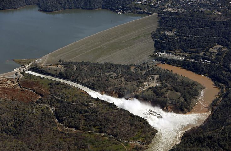"""The amount of water gushing over the main spillway at Oroville Dam was squeezed down enough by Friday for heavy equipment crews to get in and start clearing out broken concrete and other debris partially blocking the waterway, state officials said.  """"We're making great progress and are able to handle the incoming inclement weather,"""" Bill Croyle, acting director of the state Department of Water Resources, said at a daily news briefing.  Throughout the afternoon, he said, dam operators will…"""
