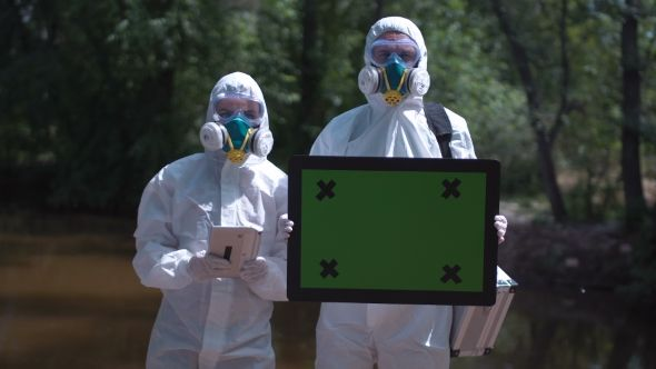 Two Ecologists in Environmental Suits by FrameStock Group of two biochemists in protective suits posing and looking at camera on background of nature and holding in hands frame with chromakey More tags people, coworkers, environment, biology, biochemistry, chemistry, teamwork, protection, suit, ecologists, equipment, biotechnology, two, scientific, research, green screen, chromakey, ecology, unifor