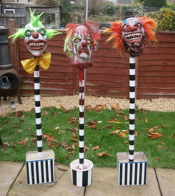 Scary clown heads on black and white spikes- this is awesome! So doing this next year! Paper mâché masks.