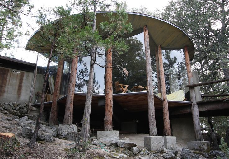 The Pearlman Mountain Cabin in Idyllwild, California, by John Lautner Architect. 1957.  Way-out deeply-cantilevered deck, on 6x18 beams. The main columns are cedar. The immense sheets of glass are let into the cedar poles. The floor is 3x tongue and groove wood planks. Note the lack of floor joists. No insulation under the floor system at all. Along the edge of the floor assembly there are steel channel irons, which are bolted to the cedar poles. Wild! According to the working drawings, the…