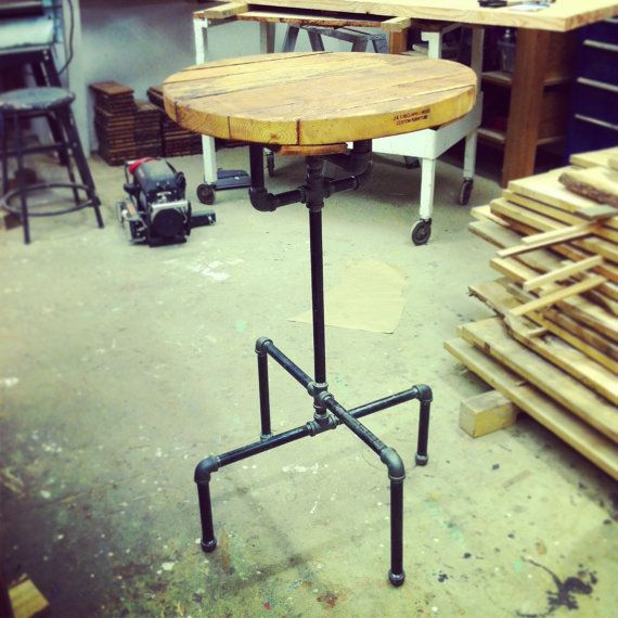 Cafe or bar table made from reclaimed wood planks and industrial cast iron pipe. Top is 2ft diameter, 1 3/4in thick rough-sawn douglas fir.