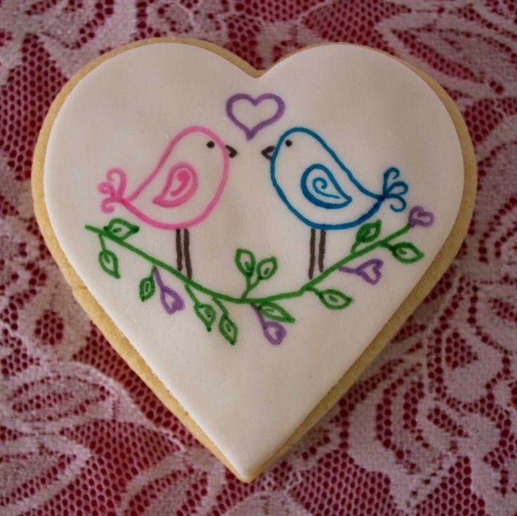 Hand-drawn love birds using edible pens on heart shaped vanilla sugar cookie