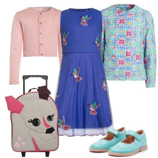 Look di primavera, con abito blu, arricchito da ricami, abbinato un cardigan rosa con bottoncini. Giacca a fantasia, sui stessi toni degli altri indumenti. Scarpa ballerina, modello bebé e trolley con cerbiatto.