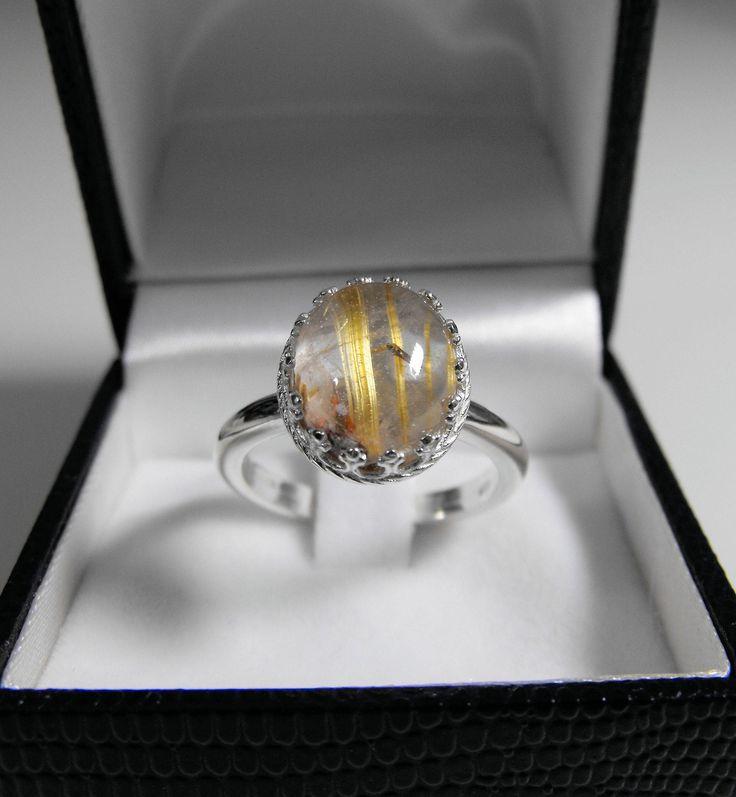 """Anello in argento 925 con quarzo rutilato, taglio cabochon, 10 x 12 mm. Il quarzo rutilato è un cristallo di rocca che presenta al suo interno aghi di rutilo (ossido di titanio) con riflessi dorati rossicci, color miele, che assomigliano a fili di capelli biondi e proprio per questa particolarità, in passato era chiamato """"Capelvenere"""" (capelli di Venere).  In questa linea di anelli abbiamo cercato di unire uno stile moderno ad uno stile classico e prezioso."""